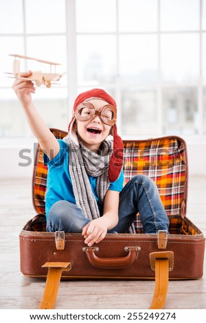 Dreaming of a sky. Happy little boy in pilot headwear and eyeglasses playing with wooden planer and smiling while sitting inside of briefcase at home  - stock photo