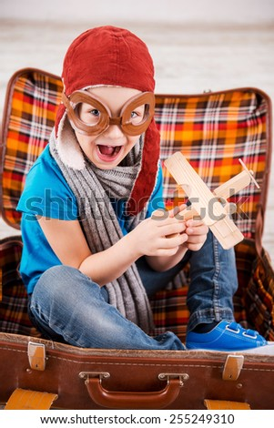 Dreaming of a sky. Top view of happy little boy in pilot headwear and eyeglasses playing with wooden planer and smiling while sitting inside of briefcase  - stock photo