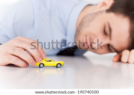 Dreaming of a sport car. Cheerful young man in shirt and tie playing with toy vehicle while sitting at his working place - stock photo