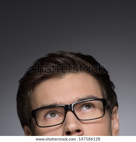 Dreaming of�¯�¿�½Cropped image of young men in eyeglasses looking up while isolated on grey - stock photo