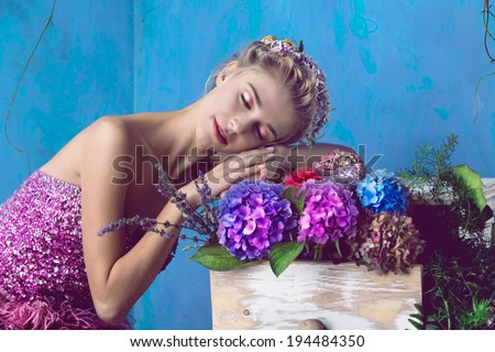 Dreaming portrait. Beautiful blond woman with braid hairstyle and natural makeup. Wearing pink bohemian sequin dress. Against blue grunge background - stock photo