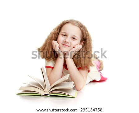 Dreaming schoolgirl with blond flowing short hair lying on the floor and reading a book - isolated on white background - stock photo