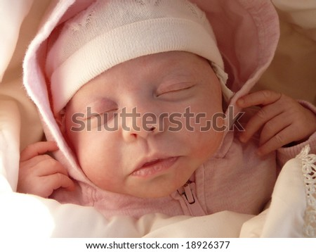 dreaming sweet baby girl in knitted bonnet and pink hood