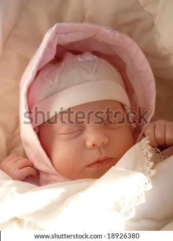 dreaming sweet baby girl in knitted bonnet and pink hood wrapped soft blanket - stock photo