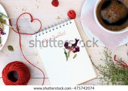 Dreaming theme: notebook with handwritten text and cup of morning coffee, bunch of grass and heart. Motivation concept in a cute romantic setting