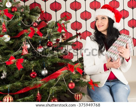 Dreaming woman holding Chrismas gift and sitting on couch home - stock photo