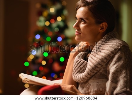 Dreaming young woman sitting chair and reading book in front of Christmas tree - stock photo