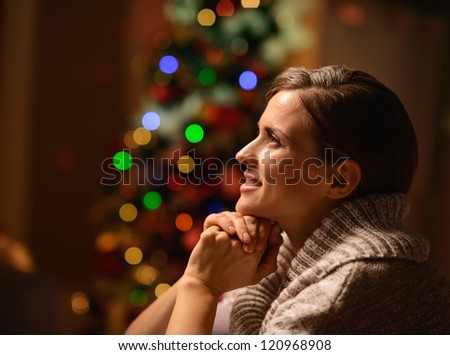 Dreaming young woman sitting chair in front of Christmas tree - stock photo