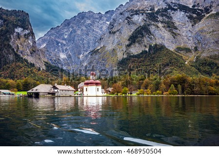 Dreamlike beauty of the Church of St. Bartholomew on the lake Konigssee. Red domes and white walls of the church reflected in the water