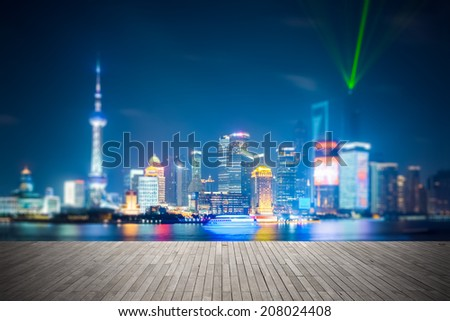 dreamlike city background of shanghai skyline at night , light show with wooden floor prospect  - stock photo