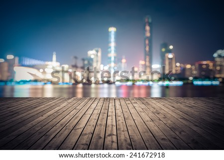 dreamlike city background of the pearl river in guangzhou at night with wooden floor as a prospect  - stock photo
