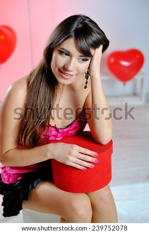 dreams of a woman on Valentine's Day with red gift in hands. - stock photo