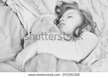 dreams of the toddler sweet girl with her bear - stock photo