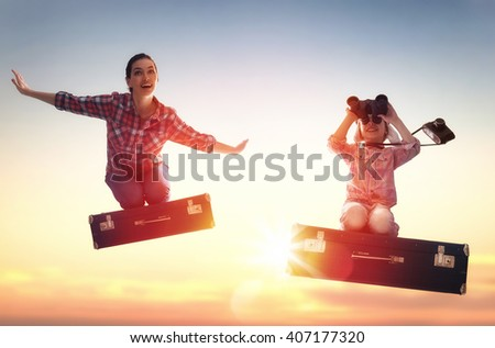Dreams of travel! Child girl and her mom flying on a suitcase against the backdrop of a sunset. - stock photo