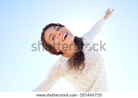 Dreamy and ethereal portrait of an attractive young woman being playful and energetic dancing with her arms raised and smiling against a sunny blue sky. Healthy outdoors lifestyle. - stock photo