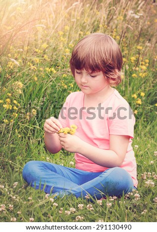dreamy beautiful young girl on field with nosegay in summer time - vintage image look - stock photo