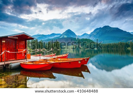 Dreamy boats stand near wooden bridge and a hut on a mountain lake on a spring day. Strbske Pleso lake, Slovakia, Tatra mountains.  - stock photo