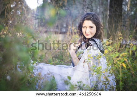 Dreamy, brunette with silver armor lying in a forest, romantic style look and old