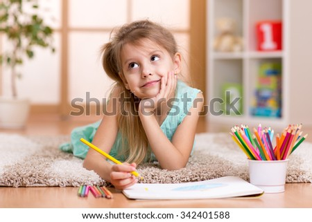 dreamy child girl draws with color pencils lying on floor at home - stock photo