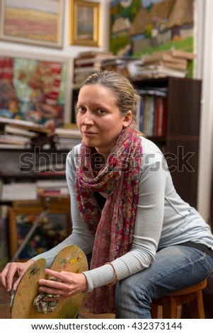 Dreamy female artist sitting in a gallery , looking at the camera and holding a colorful artists palette and paintbrush in her hand - stock photo