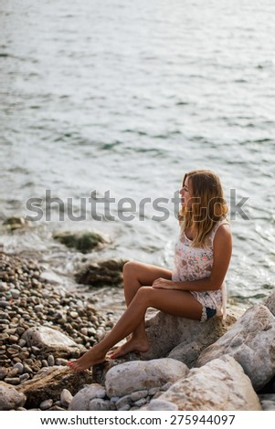 dreamy girl sitting on beach with sea view