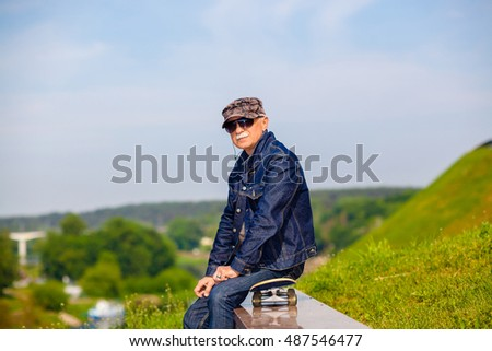dreamy hipster happy elderly man in sunglasses on blue sky background. The concept of life satisfaction. Portrait of a positive gray-haired man with a skateboard. winner concept.