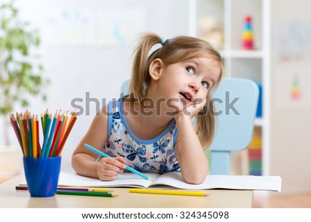 dreamy kid girl drawing with color pencils - stock photo