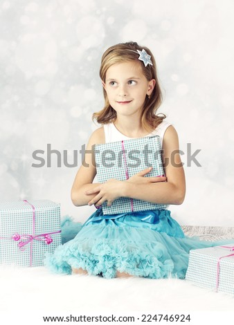 Dreamy little girl holding christmas present - stock photo