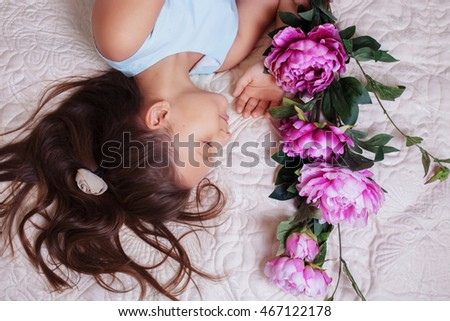 dreamy little girl with long hair lying in flowers