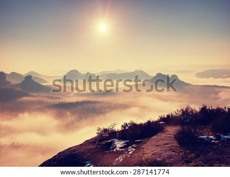 Dreamy misty landscape. Majestic mountain cut the lighting mist. Deep valley is full of colorful fog and rocky hills are sticking up to Sun. - stock photo