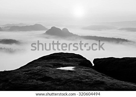 Dreamy misty landscape. Majestic mountain cut the lighting mist. Deep valley is full of colorful fog and rocky hills are sticking up to Sun. Black and white photo - stock photo