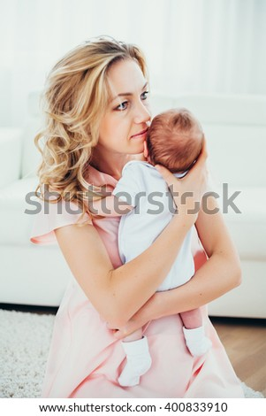 dreamy mother holding her baby (infant). family