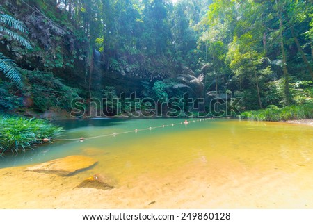 Dreamy multicolored natural pool hidden in the dense and umid rainforest of Lambir Hills National Park, Borneo, Malaysia. Concept of exploration of tropical destinations. Wide angle view from below. - stock photo