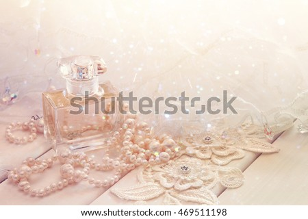 Dreamy photo of white pearls necklace and perfume bottle on toilette table. Selective focus. Glitter overlay