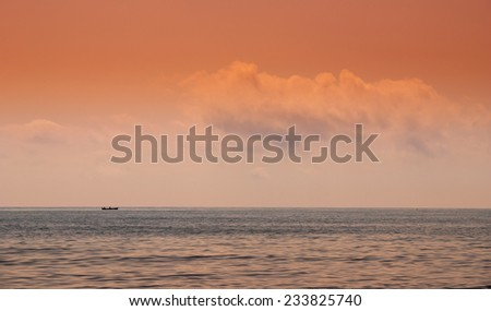Dreamy sea view with a boat at sunset - stock photo