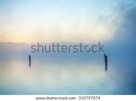 Dreamy water scenery with morning mist over calm surface - stock photo