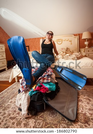 Dreamy woman in flippers holding legs on suitcase at bedroom - stock photo
