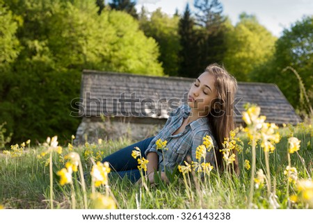 Dreamy young brunette beauty relaxing in sunset light meadow.
