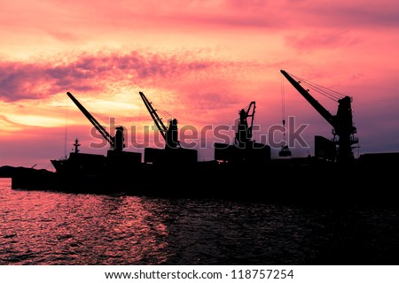 Dredge sand ship working in the sea in twilight silhouette - stock photo