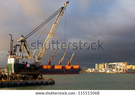 Dredger digging a shipping channel in the Port of Oakland, California.  The city's downtown buildings can be seen in the background. - stock photo