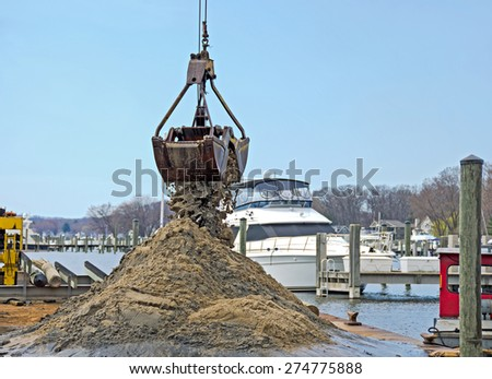 dredger dredging out a marina slip in Michigan - stock photo