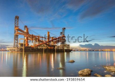 Dredger ship at sunset - stock photo