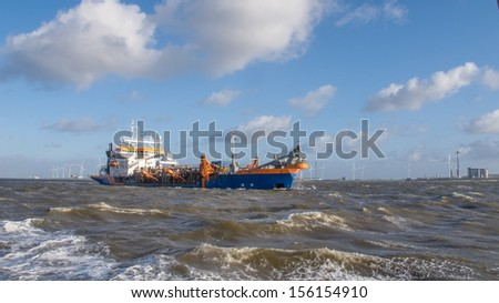 Dredging near an industrial area - stock photo