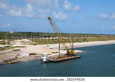 Dredging shore line and adding stone barrier wall using a barge to transport excavator - stock photo
