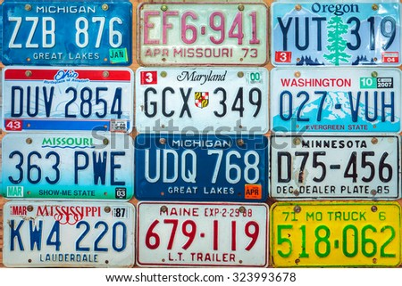 DREMPT, THE NETHERLANDS - OCTOBER 1, 2015: Vintage car license plates on a wall in Drempt, The Netherlands. In the U.S. each state issues its own car number plates. - stock photo