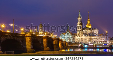 Dresden Cathedral of the Holy Trinity aka Hofkirche Kathedrale Sanctissima Trinitatis and Augustus Bridge with reflections in the river Elbe at night in Dresden, Saxony, Germany