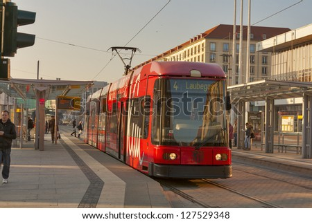 DRESDEN, GERMANY - NOVEMBER 14: A DWS 6-axle car at a tram stop with passengers on November 14, 2012 in Dresden, Germany. DVB is the municipal company which operate twelve routes on a 200 km network. - stock photo