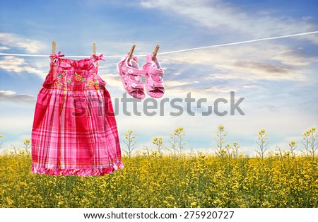 Dress and sandals on clothesline in summer fields