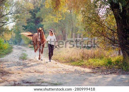 Dressage. Beautiful young woman running with her brown horse at countryside.