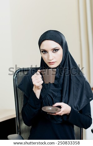 Dressed in black Muslim woman drinking coffee while sitting in an office chair - stock photo